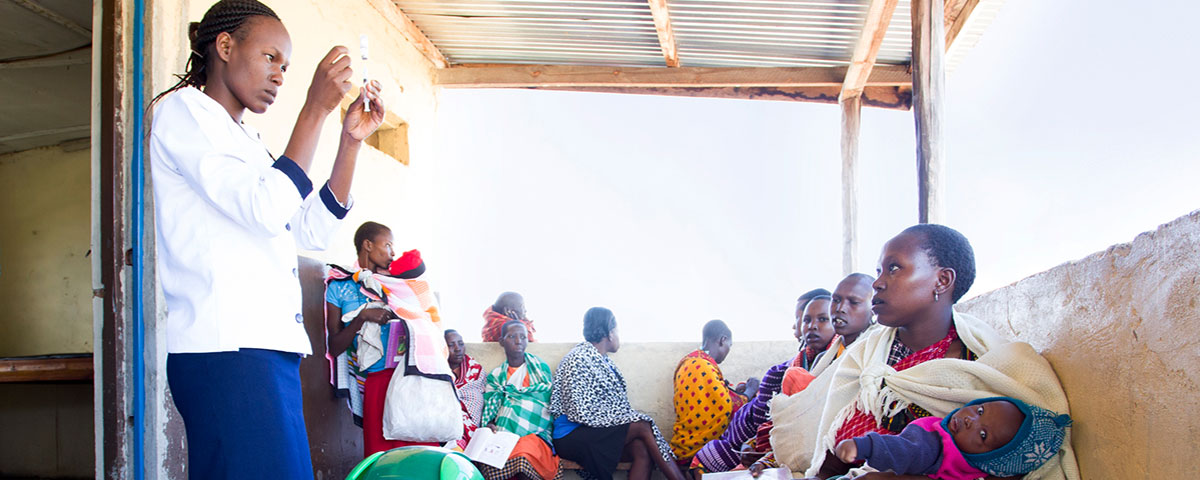 Women with their babies wait their turn to get polio vaccinations